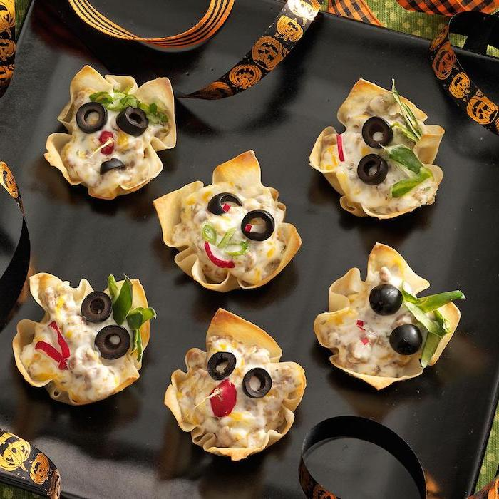 goblin bites garnished with olives chives turnip halloween snack ideas arranged on black plate