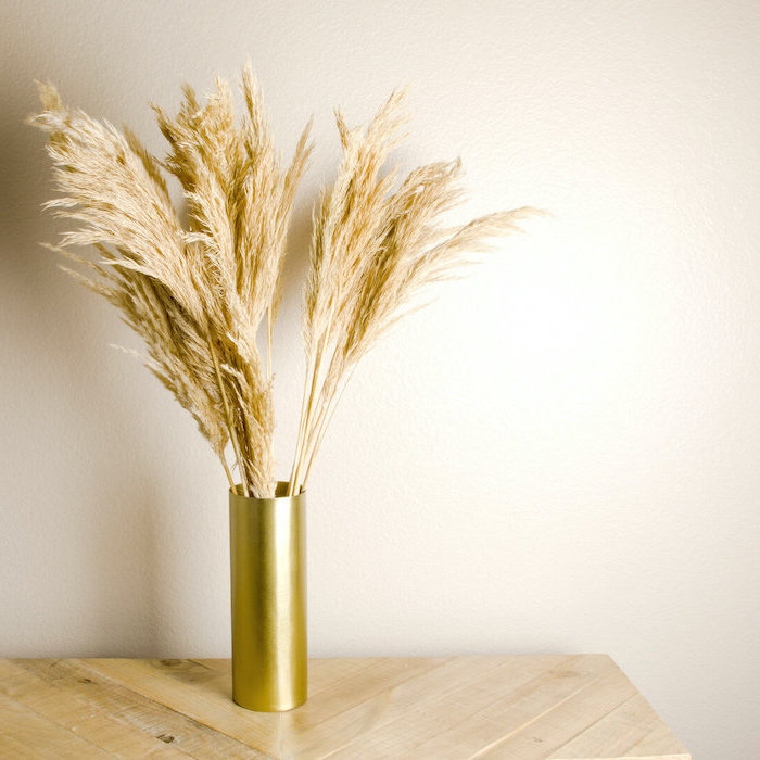 gold vase with tall pampas grass inside placed on wooden table photographed on white background