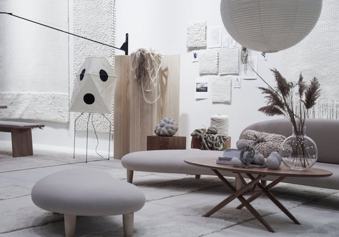 gray sofa and ottoman with wooden table in living room with white walls faux pampas grass on the table industrial style
