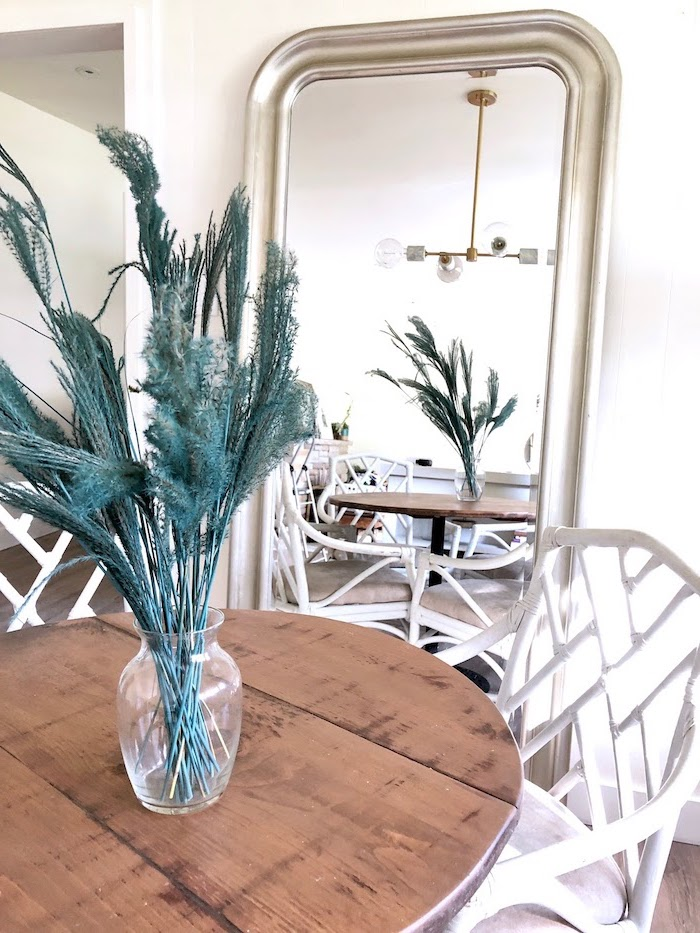 green tall pampas grass inside glass vase placed on wooden table with white chairs large mirror next to it leaning on white wall