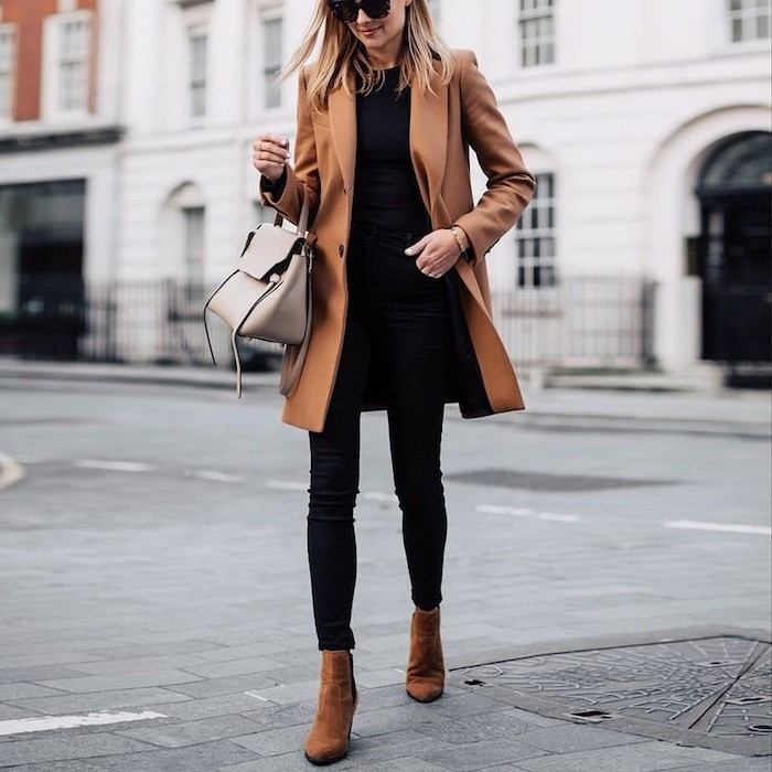grey leather bag worn by woman walking down the street cute outfit ideas black jeans t shirt brown coat