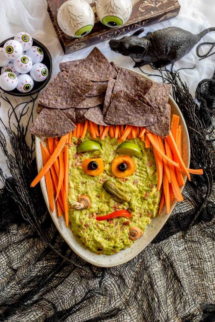 guacamole dip arranged as witch face halloween party food for adults baby carrots black tortilla chips around it