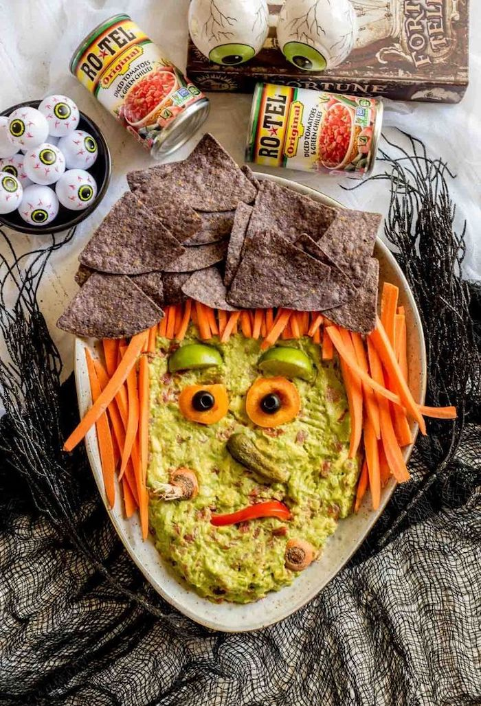 guacamole dip with baby carrots black tortilla chips halloween party food for adults arranged as with face on white platter