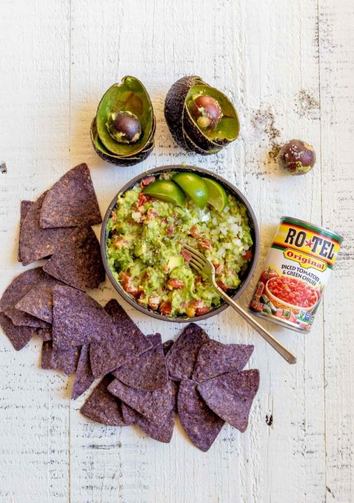 guacamole dip with tomatoes inside bowl black tortilla chips arranged on white wooden surface halloween party food for adults
