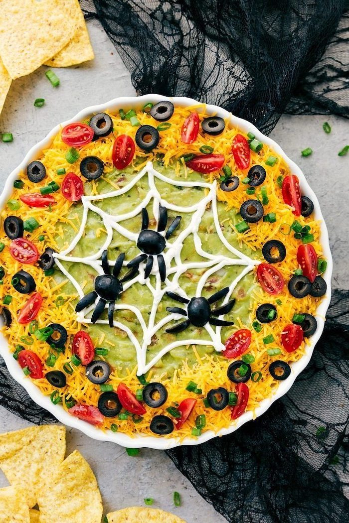 halloween appetizers guacamole dip on top of taco bake grated cheese chopped olives cherry tomatoes for garnish spider web spiders made of olives