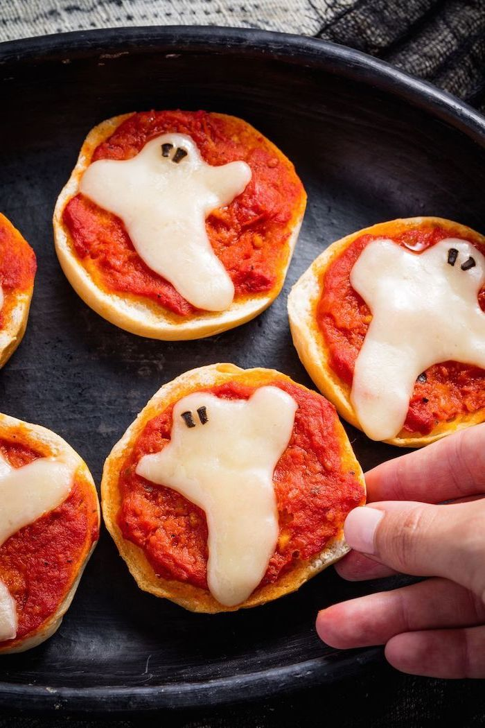 halloween finger foods mini bread bites with salsa cheese in the shape of ghosts baked in black pan
