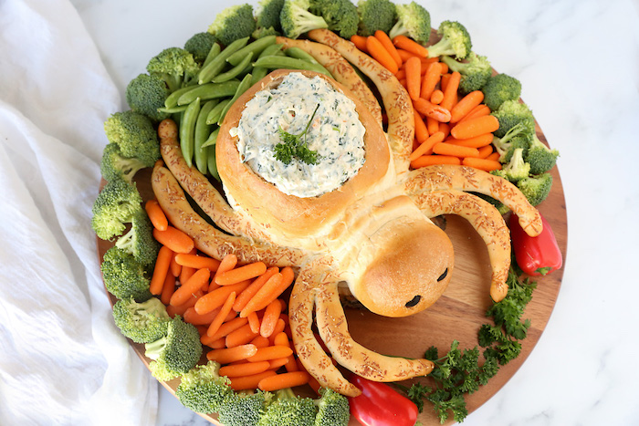 halloween party appetizers bread baked in the shape of spider baby carrots peas broccoli arranged around it on wooden cutting board