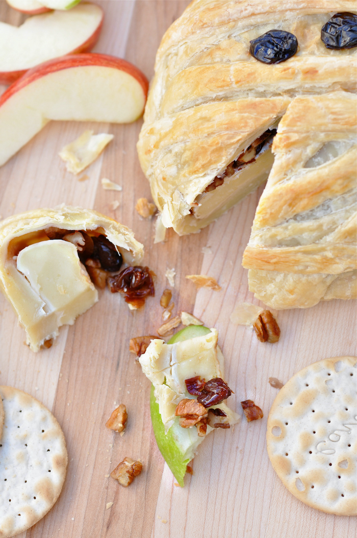 halloween party snacks baked brie with jam and walnuts baked as mummy with raisins for eyes placed on wooden surface