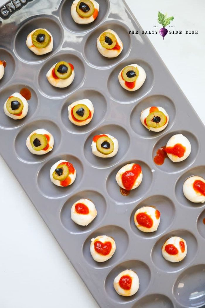 halloween party treats baby mozzarella with salsa and olives arranged in muffin baking tray placed on white surface