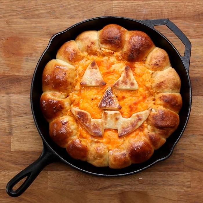 halloween snack ideas bread with melted cheese in the middle baked in black iron skillet placed on wooden surface