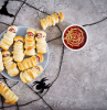 halloween themed food sausages wrapped in dough as mummies arranged on grey plate tomato dip in white bowl placed on gray surface