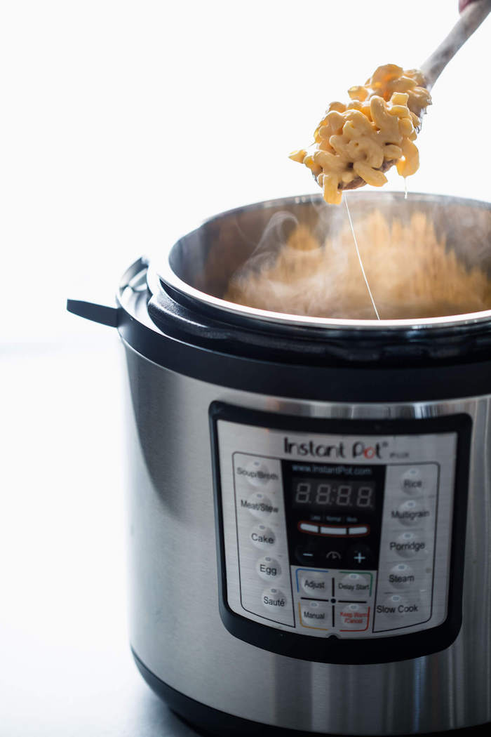 healthy pressure cooker recipes mac and cheese cooked in instant pot scooped with a wooden spoon white background