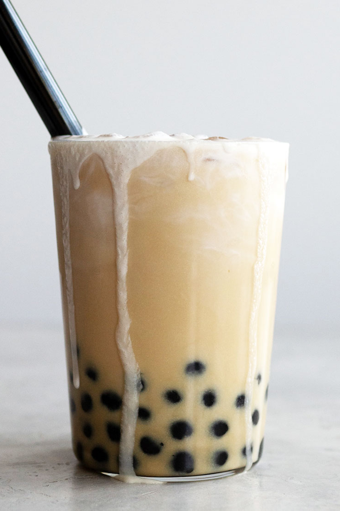 how to make bubble tea glass full of boba tea spilling out of the glass with ice and plastic straw on white background