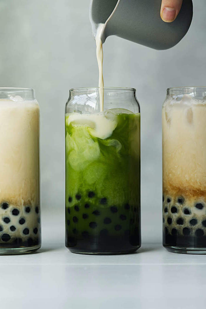 how to make milk tea milk being poured into tall glass filled with green bubble tea two more glasses next to it