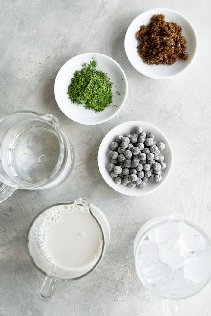 ingredients necessary for bubble tea recipe placed in white bowls and glass jugs arranged on white surface