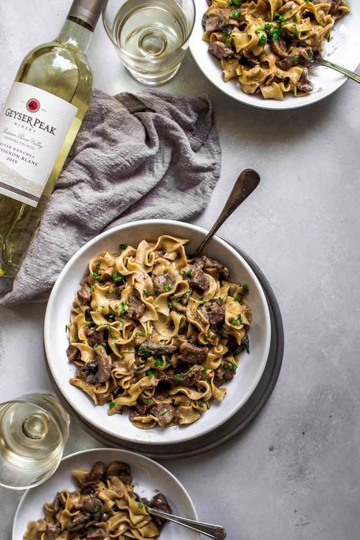 instant pot one pot meals beef stroganoff placed in white plates on granite surface glasses and bottle of wine on the side