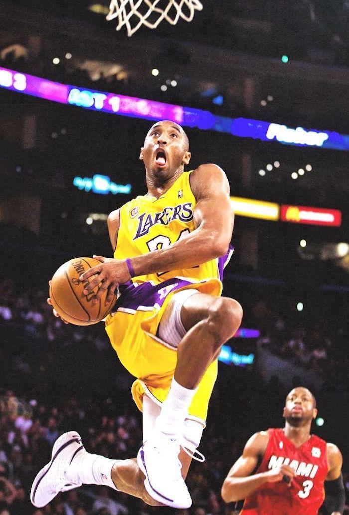 kobe bryant jumping in the air towards the basketball hoop holding a basketball kobe wallpaper wearing lakers uniform