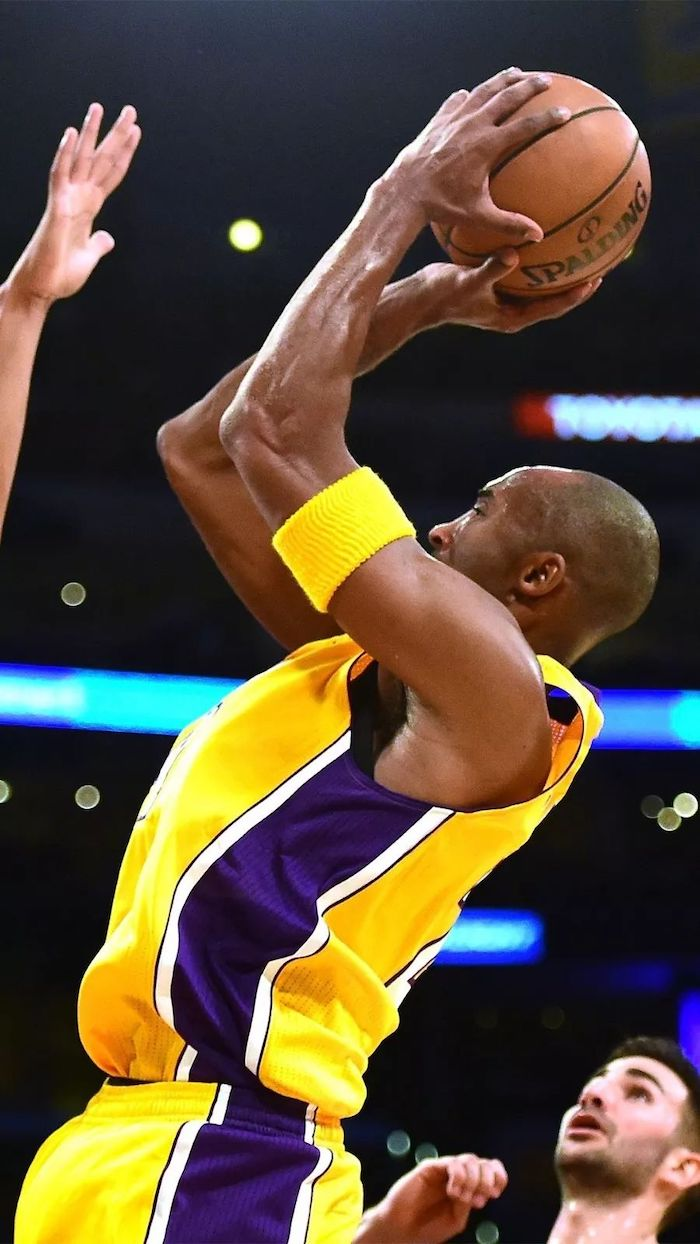 kobe bryant wallpaper holding the ball shooting in the air wearing a purple and yellow lakers uniform yellow armband