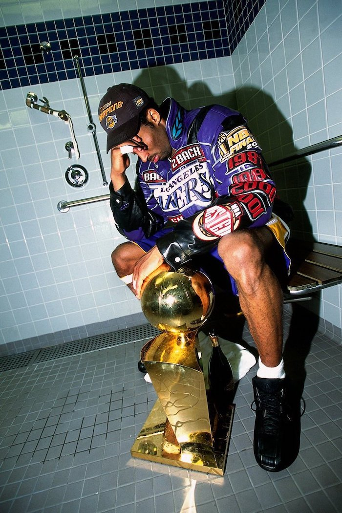 kobe sitting on a bench under showers cool kobe bryant wallpapers championship trophy on the floor in front of him wearing purple jacket