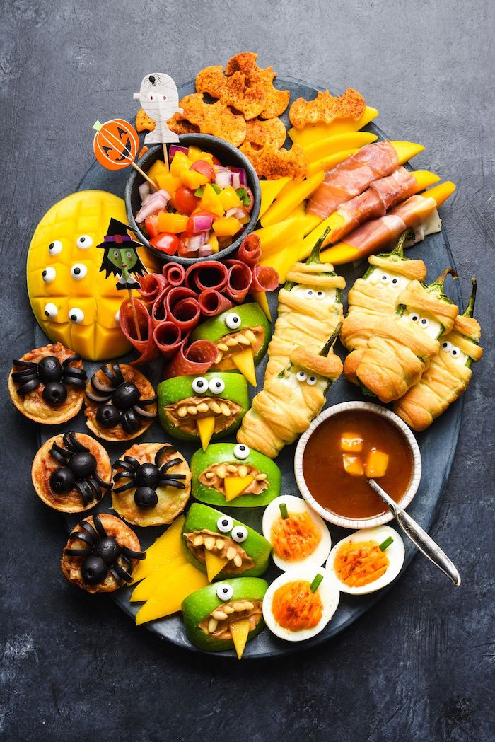 large black patter placed on gray surface halloween party treats crackers apples peppers cheese deviled eggs mango arranged on platter