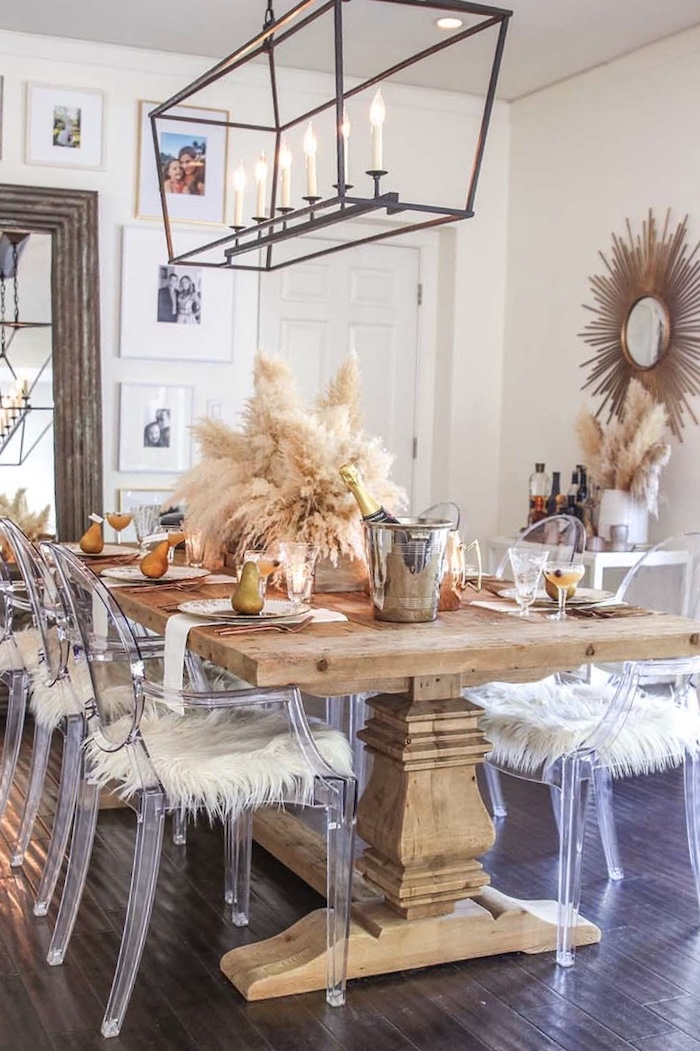 large wooden dinig table with plastic chairs colored pampas grass arrangement in the middle thanksgiving decoration