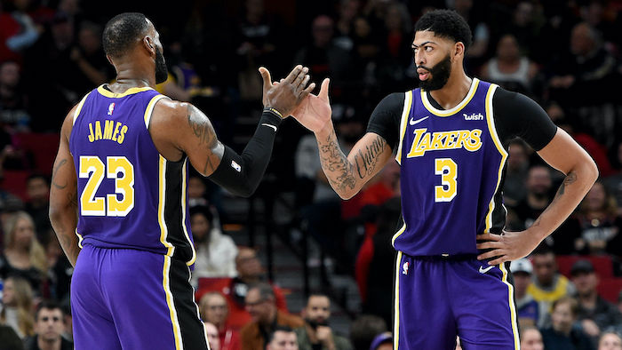 lebron james anthony davis high fiving on the court wearing lakers uniforms nba wallpaper