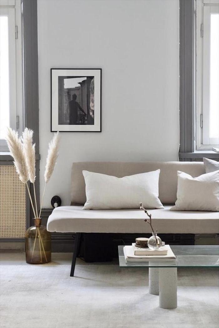 living room with white sofa glass coffee table brown glass vase with colored pampas grass inside white carpet