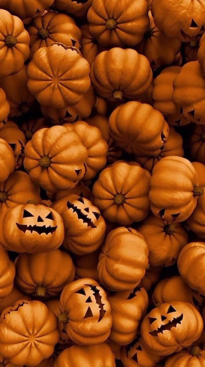 lots of pumpkins gathered together with carved spooky faces halloween phone wallpaper