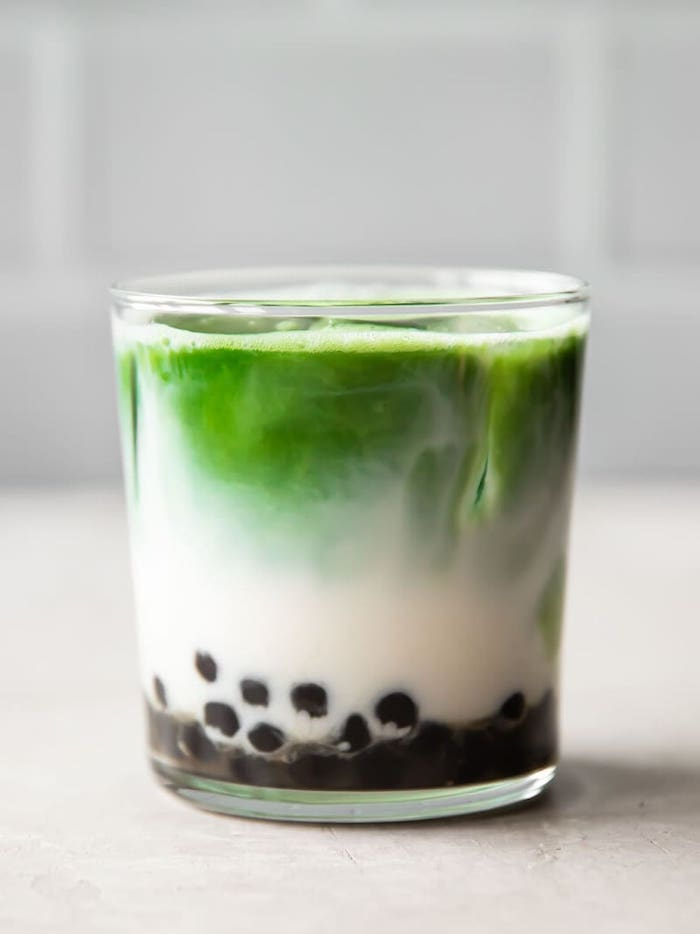 matcha bubble tea in glass filled with ice tapioca pealrs on the bottom placed on white surface how to make boba tea