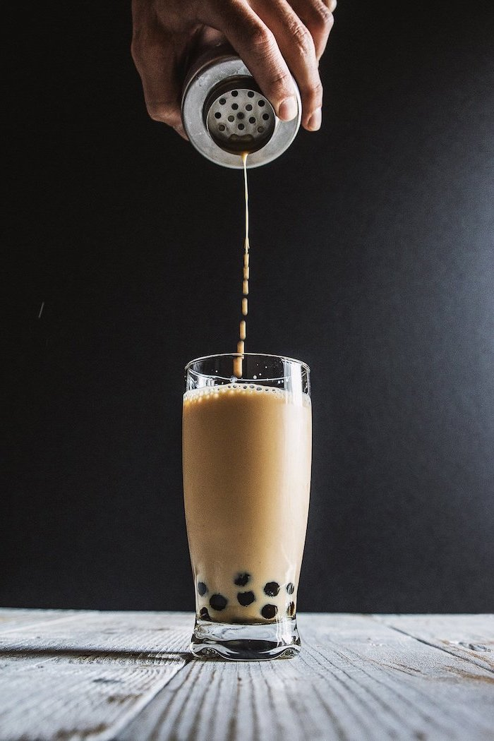 milk being poured into tall glass placed on wooden surface what is boba made of black background