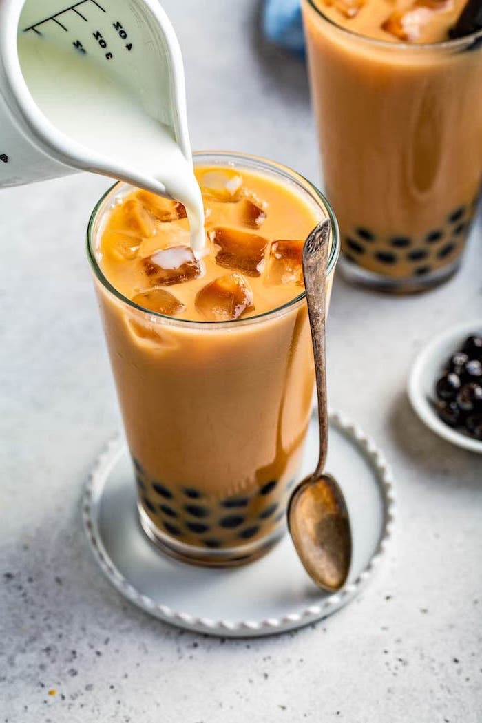 milk being poured into tall glass with bubble tea filled with ice what is boba teaspoon on the side