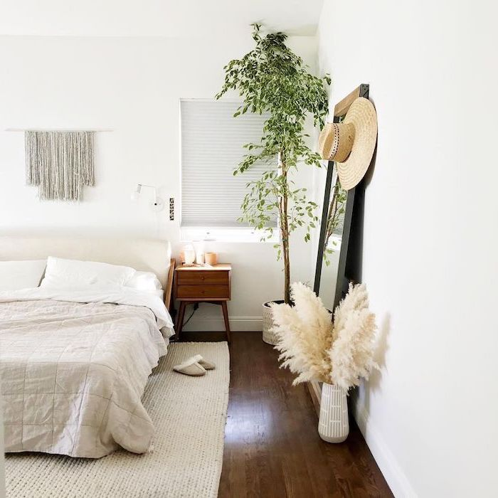 mirror leaning on white wall in bedroom with wooden floor tall pampas grass inside white ceramic vase