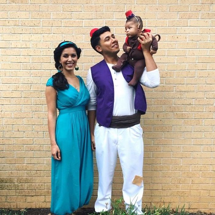 mom and dad dressed as jasmine and aladdin baby dressed as abu family halloween costumes phototgraphed in front of brick wall