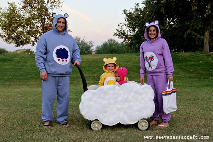 mom and dad sitting next to cart on wheels decorated as a cloud diy family halloween costumes kids inside