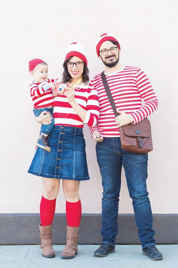mom dad and baby dressed as waldo from wheres waldo family of 4 halloween costumes photographed in front of white wall