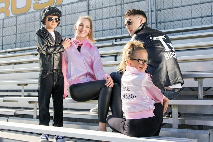 mom dad and two kids sitting in the bleachers family of 4 halloween costumes dressed as characters from grease