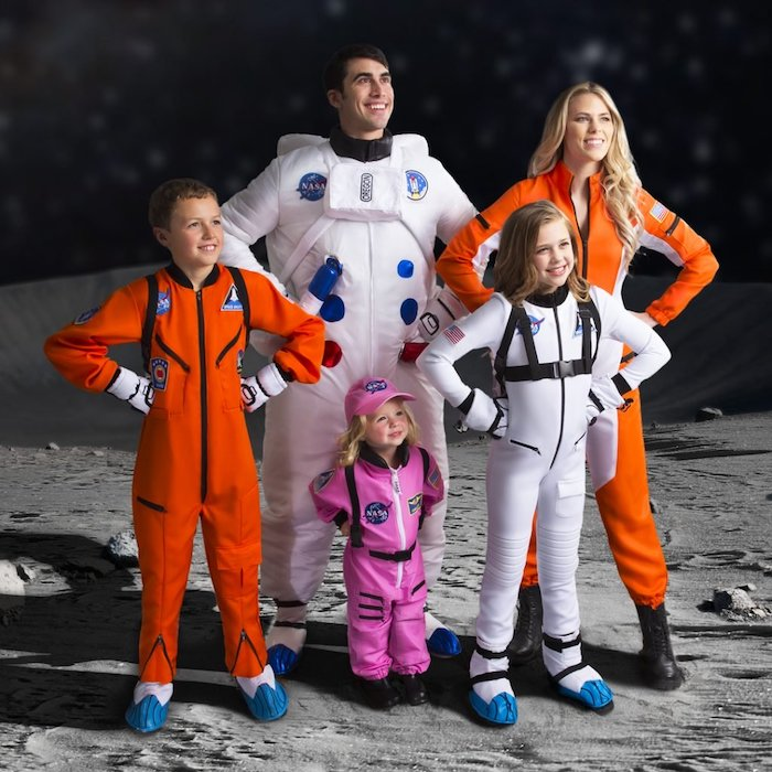 mom dad three kids dressed as astronauts photographed on background looking like the moon family of 3 halloween costumes