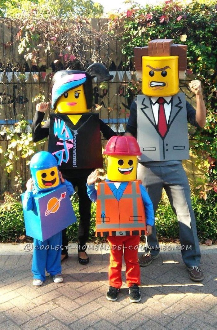 mom dad two kids dressed as lego people family halloween costume ideas standing in front of wooden wall and flower beds