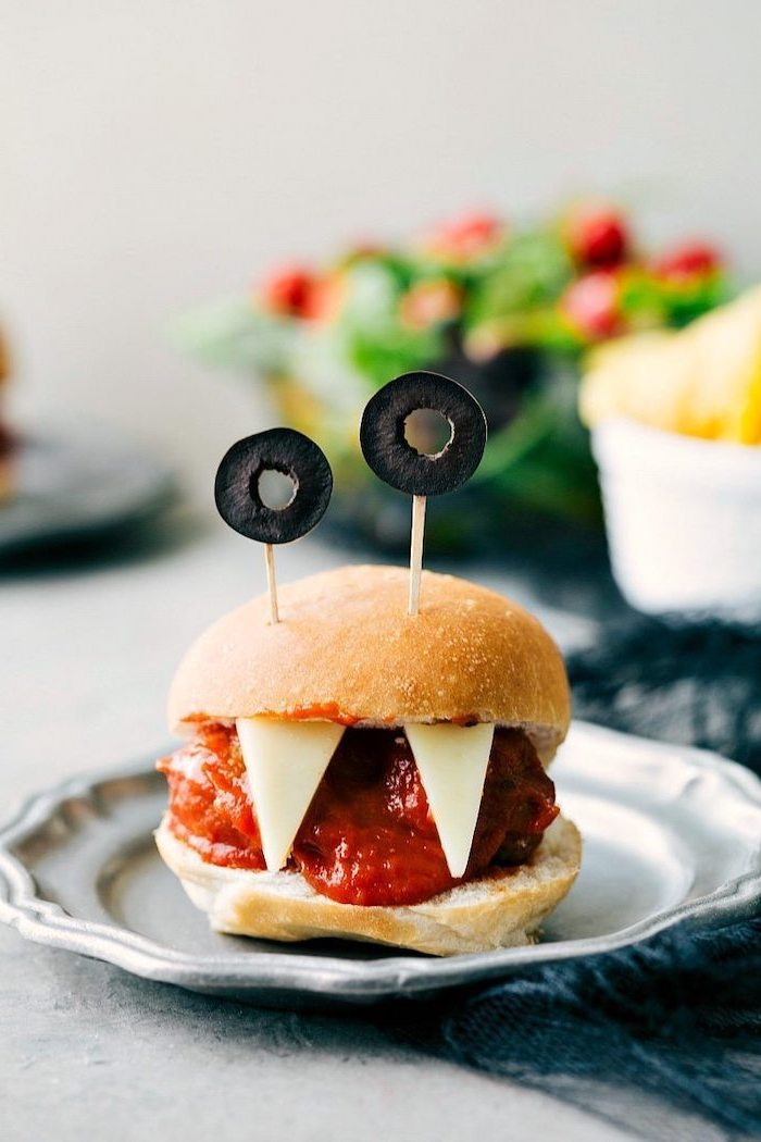 monster burger with teeth made of cheese olives for eyes halloween finger foods placed on gray metal plate