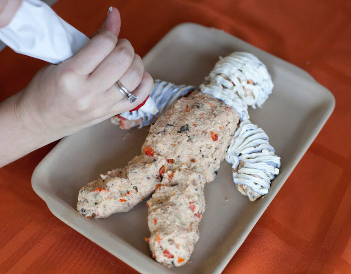 mummy made of cheese veggies halloween party snacks covered with cream cheese placed on gray baking tray