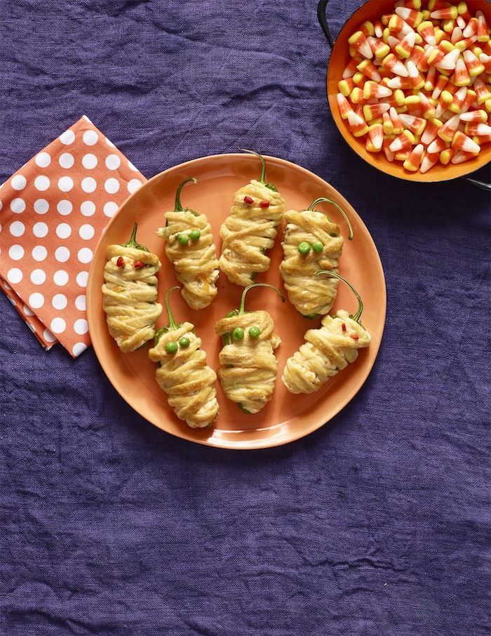 mummy peppers wrapped in dough arranged on orange plate halloween appetizers candy corn in orange plate purple table cloth