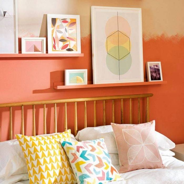 orange wall with shelves and framed art on them cozy teenage girl room colorful throw pillows on the bed with wooden frame