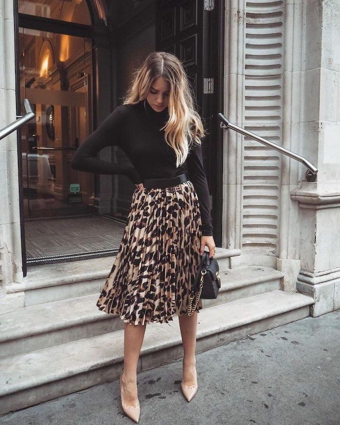 outfit ideas for women woman with long blonde wavy hair wearing leopard print pleated dress black blouse small bag