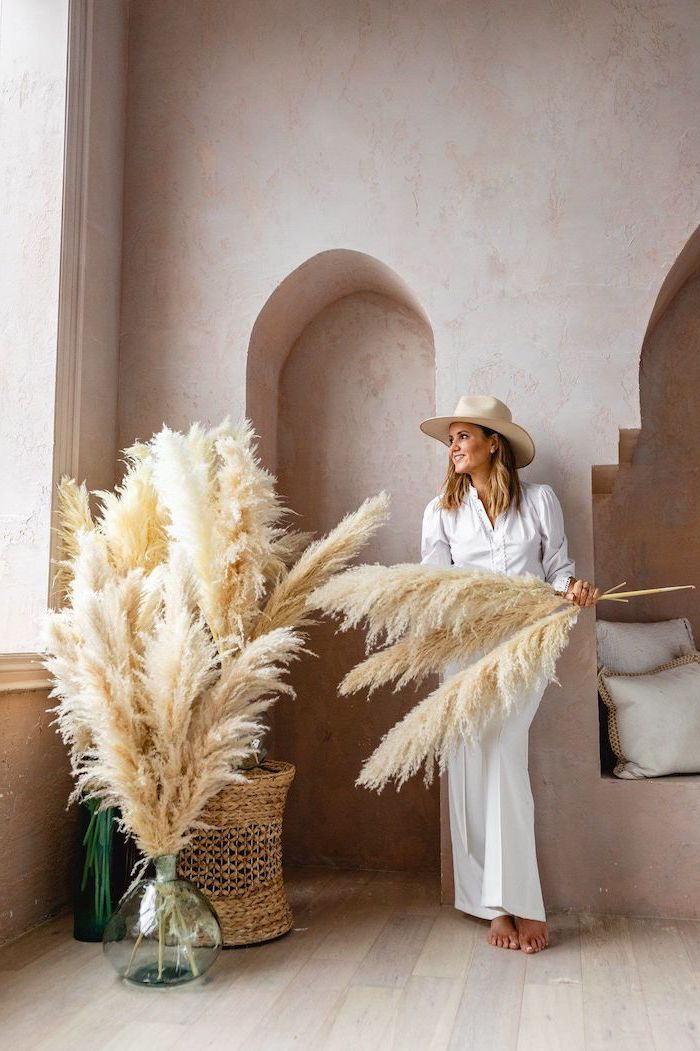 pampas grass decor woman wearing white pants shirt hat holding pampas grass standing next to vase filled with the plant