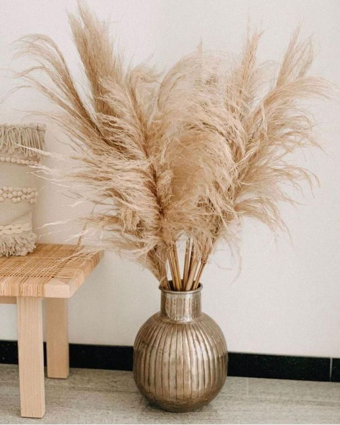 pampas grass metal round vase with the plant inside placed on tiled floor next to small wooden bench