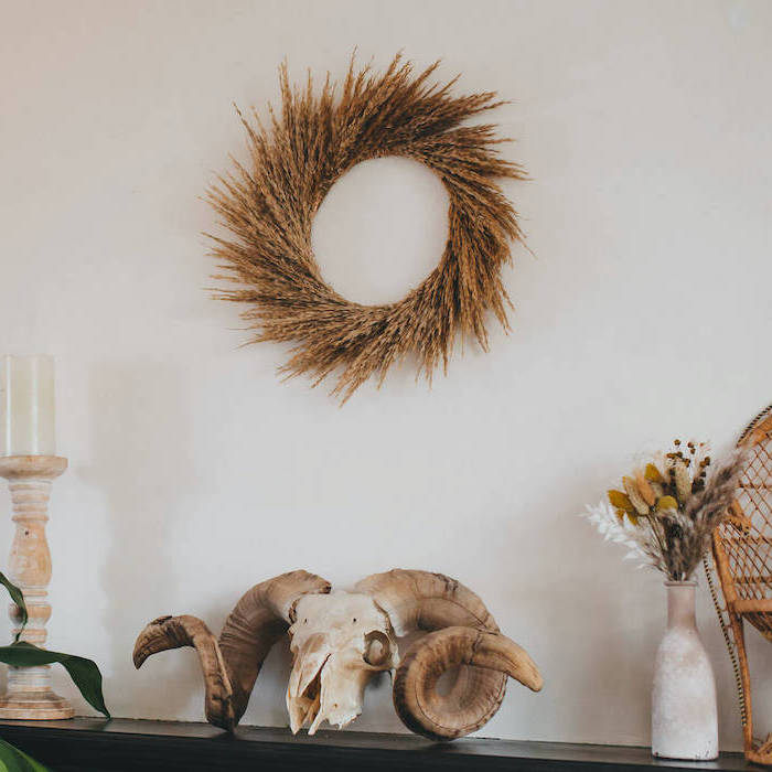 pampas grass wreath hanging on white wall tall pampas grass candle and vase on black mantel