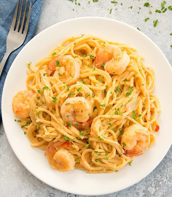 pasta with creamy sauce and shrimp garnished with chopped parsley instant pot recipes inside white plate
