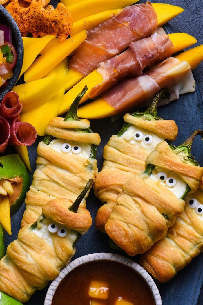 peppers wrapped with dough as mummies easy halloween appetizers cheese wrapped in prosciutto salami dip arranged on black platter