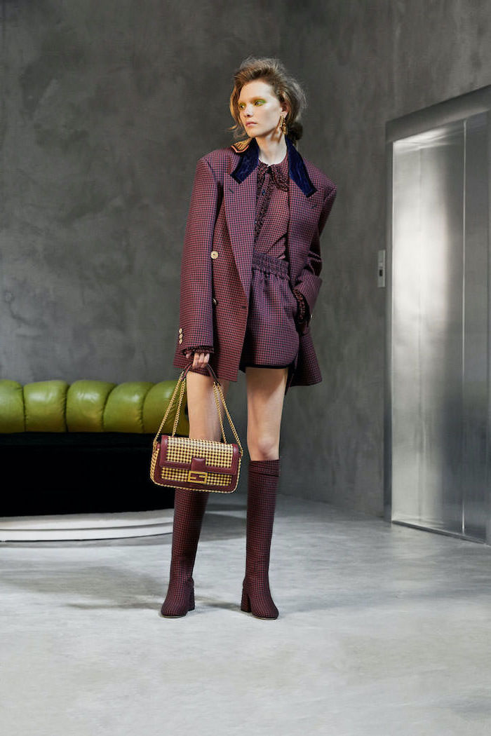 purple suit with short over sized blazer and blouse fall fashion trends matching boots and bag in yellow and purple worn by woman with dark blonde hair