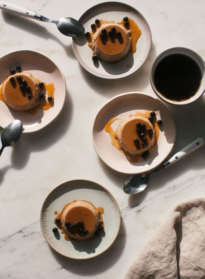 recipe for flan with tapioca pearls what is boba tea flans placed on white ceramic plates arranged on marble surface spoons next to them